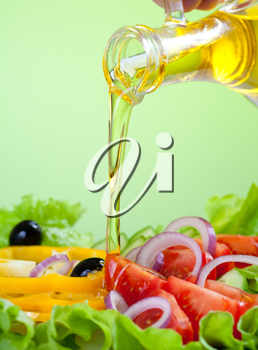 Royalty Free Photo of a Person Putting Oil on Their Salad