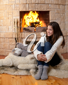 Royalty Free Photo of a Teenage Girl Beside a Fireplace