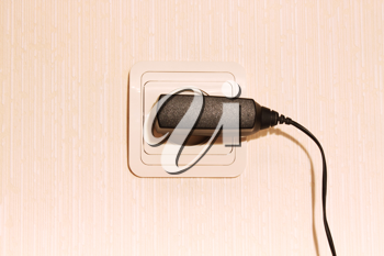 Beige wall plug with a cable for a mobile phone