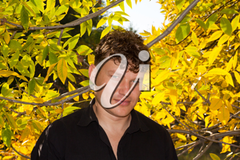 man in a black shirt on the background of autumn