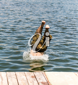 A man dives from shore to lake .