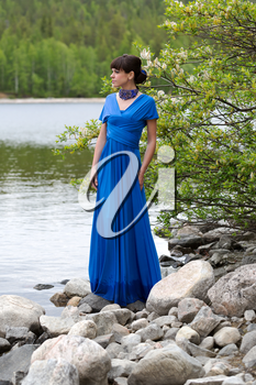 Girl in blue evening dress on a blue lake