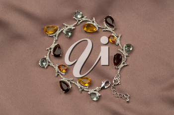 Precious bracelet with stones on a satin brown background