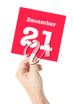 December 21 written on a card held by a hand