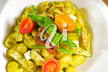 fresh lumaconi pasta and pesto sauce with vegetables and sundried tomatoes,tipycal italian food