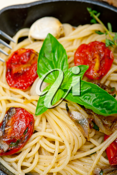 italian spaghetti pasta with baked tomatoes  basil and thyme sauce on a cast iron skillet