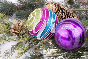 Christmas decoration with balls, cone and fir-tree branch.