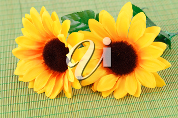 Yellow fabric flowers on bamboo background, closeup picture.