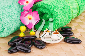 Spa set with towels, candles, stones and flowers on bamboo background.
