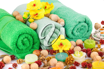 Spa set with towels, candles, wooden balls and flowers closeup picture.
