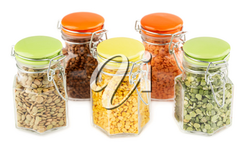 The collection of different groats in the glass jars isolated on white background. Split peas, buckwheat and colorful lentils.