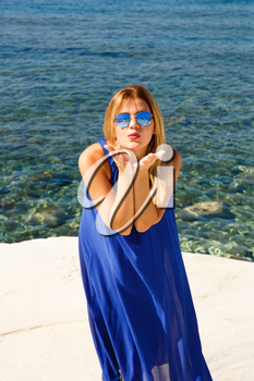 Blond woman in the blue dress at the beach in Cyprus.