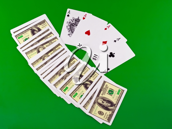 Four aces and dice on green broadcloth (background).