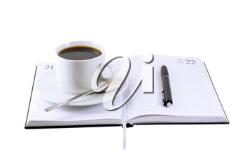 Coffee cup, standing on the opened daily organizer . Isolated