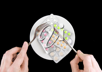 Coloured pills in white plate with fork and spoon in hands, on black background.