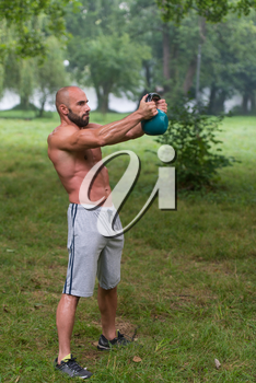 Fitness Man Lifting Kettlebell Workout Exercise Outdoors In Nature