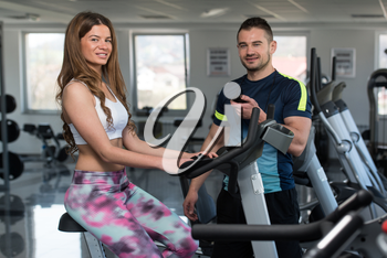Young Woman In The Gym with Personal Trainer - Exercising Her Legs Doing Cardio Training On Bicycle