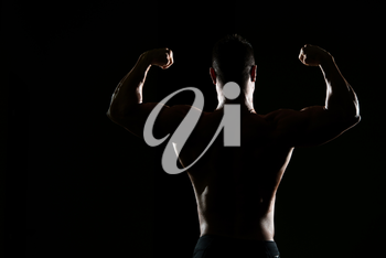 Silhouette Portrait Of A Young Physically Fit Man Showing His Well Trained Body - Muscular Athletic Bodybuilder Fitness Model Posing After Exercises
