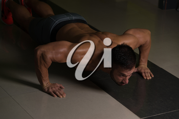 Muscular Adult Athlete Doing Push Ups As Part Of Bodybuilding Training