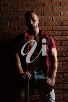 Healthy Young Man Standing Strong In The Gym And Flexing Muscles While Wearing Plaid Shirt - Muscular Athletic Bodybuilder Fitness Model Posing After Exercises On Wall of Bricks