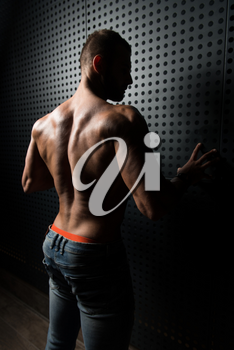 Healthy Young Man Standing Strong Standing Against a Wall and Flexing Muscles While Wearing Blue Jeans - Muscular Athletic Bodybuilder Fitness Model Posing After Exercises - a Place for Your Text