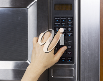 Hand preparing to activate defrost mode on microwave oven