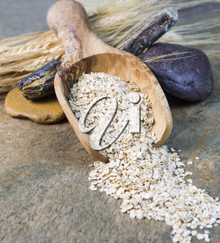 Vertical photo of rolled oats in wooden spoon with rocks and wheat stalks on natural stone