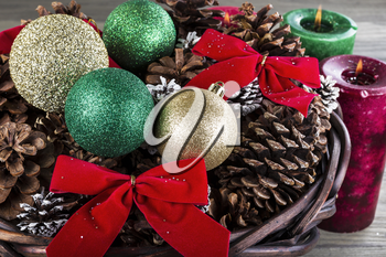 Holiday basket containing red ribbons, dry pine cones, gold and green ornaments and candles with flame in background