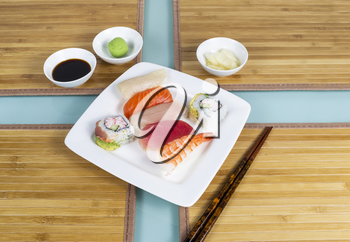 Variety of fresh sushi on white plate with chop sticks, soy sauce, wasabi mustard and ginger slices on bamboo place mats on table
