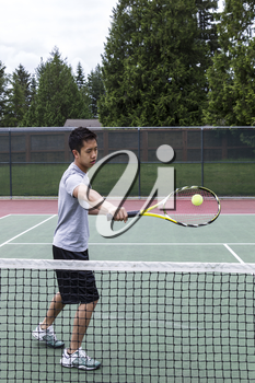 Young Asian Man using backhand volley on outdoor tennis court