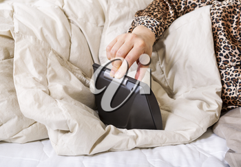 Horizontal photo of female hand pushing down switch on alarm clock to turn it off