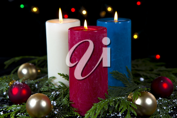 Colorful candles in white, red, blue in seasonal setting on black background