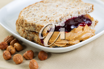 Closeup horizontal photo of a peanut butter and jelly sandwich cut in half, inside white plate with whole nuts lying on textured table cloth