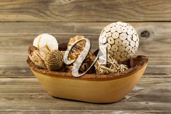 Closeup horizontal photo of home decorations place inside of a wood basket on rustic wooden boards