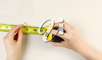 Horizontal photo of female hands using tape measure and pencil on interior home white wall