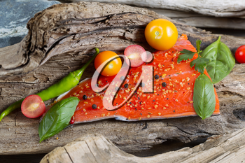 Horizontal view of raw salmon fillet, skin side down, with seasoning inside of drift wood