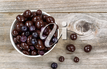 Overhead shot of dark chocolate and blueberries in white bowl on rustic wood