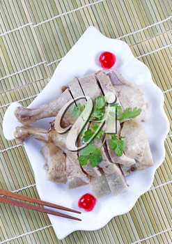 Vertical top view image of Chinese cooked chicken, parsley, cherry and chopsticks in shell shaped white plate with natural bamboo place mat background