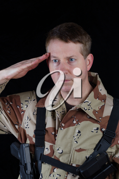 Vertical image of military male soldier saluting while armed with black background.