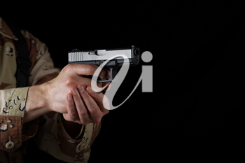 Close up horizontal image of pistol, pointing sideways into darkness, with armed male soldier in background. Focus on side part of weapon.