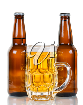 Golden colored beer in stein with two full bottles in background. Isolate on white with reflection.