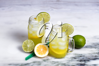 Front view of fresh lemonade and lime in jar glasses on white marble stone.  Selective focus on upper lip of front glass and lime slice.