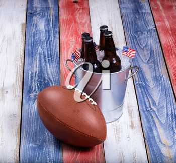 Top view of American football and bucket of ice cold beer on rustic wooden boards painted in USA national colors.