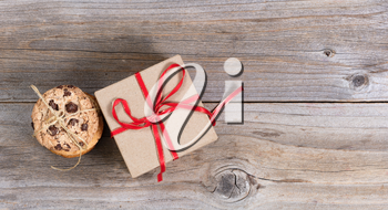Overhead view of freshly baked cookies, tied with string, and a boxed gift with ribbon on rustic wood.