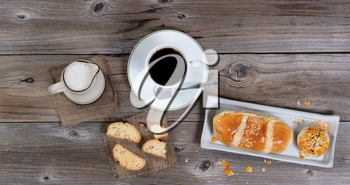 Freshly baked pastries with coffee and cream on rustic wooden table. Flat layout.