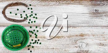St Patricks day good luck hat and horseshoe with shiny clovers forming border on left side of rustic white wooden boards