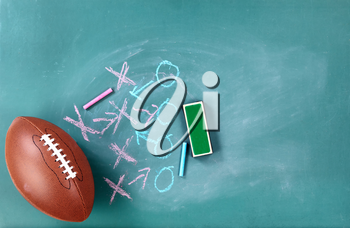 American football with game plan written on cleaned chalkboard
