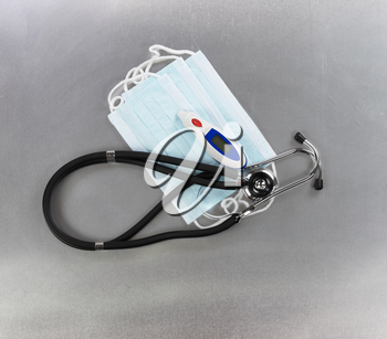 Personal mask, thermometer and stethoscope on stainless steel background for protection against virus or flu concept