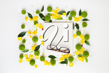 Glasses and paper with pattern from petals of roses and chrysanthemum flowers, ficus leaves and ripe rowan on white background. Overhead view. Flat lay.