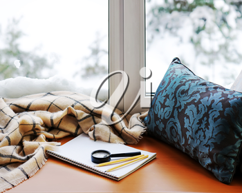Open notepad, magnifier glass, pillow, pencils and beige warm plaid located on stylized wooden windowsill. Winter concept of comfort and relaxation.